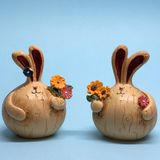 Small figures of two hares with flowers on a blue background stock images