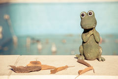 Small figurine of a cute crocodile at the edge of an empty swimming pool. Autumn concept Stock Image