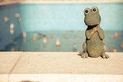 Small figurine of a cute crocodile at the edge of an empty swimming pool. Autumn concept Royalty Free Stock Photography