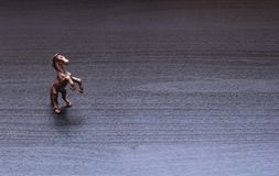 A small figurine of a horse. On a gray brown background Royalty Free Stock Images