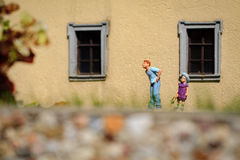 Small figurine. Two children play in garden royalty free stock images