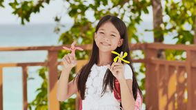 A small filipino schoolgirl shows spinning spinners. Tropical landscape. Summer. Childhood. A small philippine schoolgirl shows spinning spinners. Tropical stock footage
