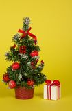 Small fir-tree in a pot with toys and gifts Royalty Free Stock Photos