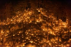 Small fires in a rocky hill with trees during a light celebration in the Frankonian Alb, Southern Germany stock photography
