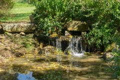 Small Fish Pond and Waterfall. A small fish pond and waterfall located in small public park royalty free stock photography