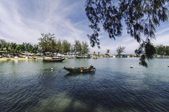 Small fisherman boats anchored at the shore with blue sky and soft clouds Stock Images
