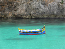 Small fisherman`s boat. Colorful fisherman`s eyed boat called `Iuzzu` tipical of Malta anchored in a crystal clear water bay in Gozo Royalty Free Stock Photography