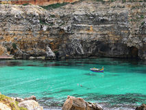 Small fisherman's boat in a wonderful bay Gozo Malta. Colorful fisherman's eyed boat called Iuzzu tipical of Malta anchored in a crystal clear water bay in Gozo Stock Photos