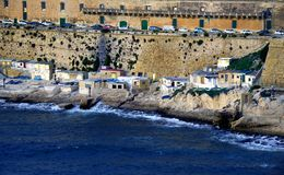 Small fisherman`s village in Valletta,Malta. Small Fisherman`s houseson the rocks in Valletta,Malta with coastline,view from the Sea Royalty Free Stock Photos