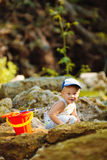 Small fisherman sits with fishing rod Stock Image