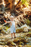 Small fisherman sits with fishing rod Royalty Free Stock Photos