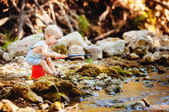 Small fisherman sits with fishing rod Stock Photo