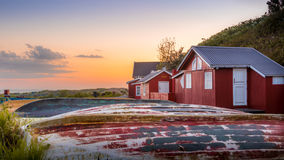 Small fishermen houses with dinghies laying upside down in the grass at sunset. At the harbor of the city of Boderne, on the island of Bornholm, Denmark. May 26 stock photography