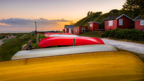 Small fishermen`s houses with dinghies laying upside down in the grass at sunset Stock Photos