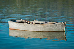 Small fishing boat. Old and worn out small wooden fishing boat on sea Royalty Free Stock Photos