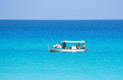 Small fishing boat in a calm blue sea. View of a small fishing boat in a calm blue sea Royalty Free Stock Images