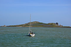 Small fishing boat departs from port landscape Stock Images