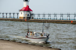 Fishing boat and light house. A small fishing boat drives into the harbor near the saint Joseph light house in st Joe Michigan Royalty Free Stock Images