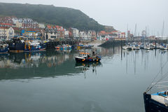 Small fishing boat entering Scarborough harbour Stock Photos