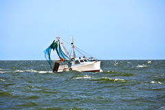 Small fishing boat heading out to the ocean Stock Image