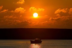 Small fishing boat on its way out to sea at sunset Royalty Free Stock Photos