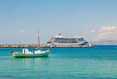 A small fishing boat and large cruise ship Stock Image