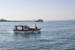 Small fishing boat leaving from Kadikoy. In Istanbul. Modern ferry is in the background Royalty Free Stock Photos