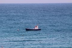 Small fishing boat in the middle of the open sea. Stock Images