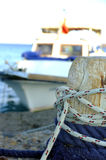 Small fishing boat moored to wooden pole Stock Image