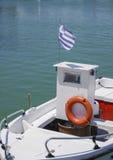 Small fishing boat with orange lifebuoy and Greek flag waving. Stock Image