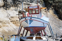 A small fishing boat out of the water, for repairs, in Vlychada village, Santorini island Stock Photos