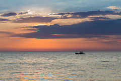 Small fishing boat over seacoast skyline with sunset background Royalty Free Stock Image
