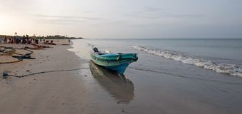 Small fishing boat reflecting in sunset light on Nilaveli beach in Trincomalee Sri Lanka stock image