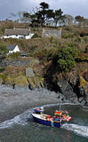 Cadgwith Cove Cornwall. A small fishing boat returns to Cadgwith Cove on the Lizard peninsula in south west Cornwall Stock Photography