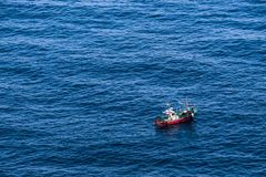 A small fishing boat sailing the blue water of the sea stock image