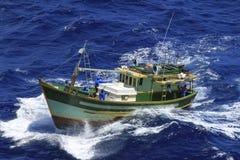 Small fishing boat at sea. Small fishing boat, white, green and orange deep sea stock photos