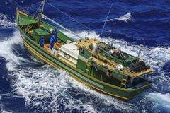 Small fishing boat at sea. Small fishing boat, white, green and orange deep sea Royalty Free Stock Images
