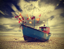 Small fishing boat on shore of the Baltic Sea, vintage retro. Royalty Free Stock Image