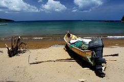 Small fishing boat on the shore in front of the beautiful sea. In the Caribbeans Royalty Free Stock Photos