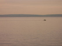 Small fishing boat. Silhouette in soft orange light royalty free stock photo