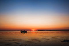 Small Fishing Boat at Sunset in Eastham, Cape Cod Massachusetts. A small fishing boat in the brilliant orange Cape Cod sunset in Eastham, Massachusetts Stock Photography
