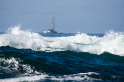 Small fishing boat with surf Stock Image