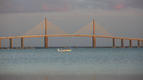 Small fishing boat under the Sunshine Skyway Bridge - Florida. Small fishing boat under the Sunshine Skyway Bridge - Fort DeSoto Park, Florida stock photography