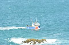 Small fishing boat wityh rock in foreground Stock Photos