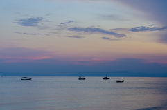 Small fishing boats anchor near bay Stock Photos