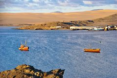 Luderitz bay, Namibia. Small fishing boats in bay of Luderitz at sunset. Luderitz is a harbour town lying on one of the least hospitable coasts in Africa Stock Photos