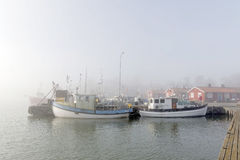 Small fishing boats in the harbor a foggy morning Royalty Free Stock Photography