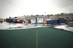 Small Fishing Boats in Mousehole Harbour. A few fishing boats in Mousehole Harbour at high tide. Photo taken on a cloudy summer`s day Royalty Free Stock Photography