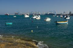 Boats And Industrial Port, Malta. Small fishing boats near Birzebbuga, the big freeport in the background Stock Images