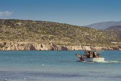 Small fishing boats off the coast in one of the bays. Stock Photography